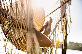 Back view of relaxed woman in hammock during summer day.