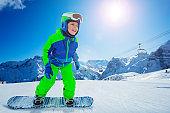 Snowboard boy move fast on the ski resort hill