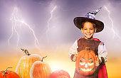 Happy little boy hold spooky Halloween pumpkin