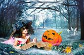 Girl in witch costume cast spells over big pumpkin