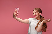 Funny young redhead woman making selfie. Smiling girl wearing white t-shirt holding pink smartphone, making faces on camera, posing for selfie isolated on pink background