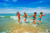 Group of cute kids run from sea holding hands