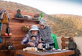 Two cheerful senior people enjoy a break with food and drinks after a hike in the mountains. Wooden table with cheeses, salami and red wine. 70 year old couple.