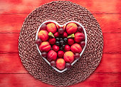 Appetizing plate of seasonal ripe fresh fruit in a white heart-shaped plate - healthy eating with apricots, grapes, strawberries, blueberries and kiwis - Wooden fuchsia color background