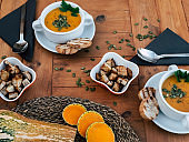 Two white bowls with a tempting ready-to-eat pumpkin cream soup with croutons over a rustic wooden table. Vegetarian or vegan lifestyle for healthy eating