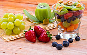 A glass cup with healthy fresh colorful fruit salad ready to eat. Wooden background with kiwi grapes strawberry and blueberries