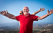 Two senior friends people enjoying freedom standing on hill with mountain and city on background looking at camera with arms raised - active seniors and vacation concept