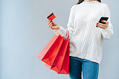 Cropped shot of female customer wearing cozy knitted white sweater and holding bunch of shopping bags, moblile phone and credit card in hands