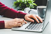 Close up cropped shot of male hands typing on keyboard and surfing touchpad