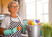 elderly woman busy with house hygiene works stops for a coffee break - precautions against virus infection