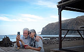 Happy senior couple looking at mobile phone in sea excursion. Cup of coffee together on the beach at a wooden table.  Concept of active elderly vacation. two retired people together
