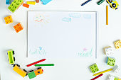 Top view of a white table with pencils, toy train, lots of colorful plastic block and an album with children's drawings. Layout. Children's drawing table.