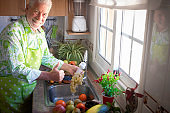 Senior man washing a bunch of grapes. Background with different kind of fresh fruits.  Healthy eating concept and detox diet. Vegan and vegetarian food.