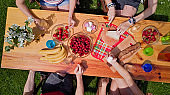Family and friends eating together outdoors on summer garden party. Aerial view of table with food and drinks from above. Leisure, holidays and picnic concept