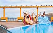 Eight beautiful female friends standing close to the swimming pool  with inflatable mattress. Bikini and swimsuit. Blue water and sunlight. Concept of friendship and vacation