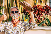 A senior woman wearing a flowered protective face mask due to coronavirus standing in a tropical garden making ok sign with hand. An old retired people with a straw hat looking at camera