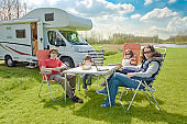 Family vacation, RV travel with kids, happy parents with children have fun on holiday trip in motorhome, camper exterior