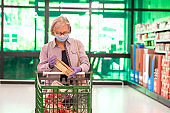 Alone senior woman with gray hair and glasses while pushs a shopping cart in the supermarket choosing food and drink