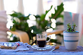 Espresso coffee in a glass cup, outdoor on balcony with plants and chairs - chocolates and sugar cane  on background