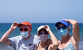 A group of three senior people enjoying beach holidays together holding hats that the wind blows away, wearing a mask because of the coronavirus - active retired seniors and new normal concept