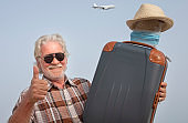 Smiling traveler senior man holding his suitcase ready to flight for summer vacation with surgical mask to procect himself from coronavirus Covid-19 - enjoying lifestyle and freedom concept