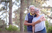 An elderly pretty couple outdoors in a green forest. Two senior adult people celebrate Valentine's Day with joy and hugs