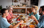 Happy group of family shares food and drinks at home, having fun together. Table with vegetarian food. Grandmother with son, daughter-in-law and grandson