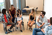 Group of young Brazilians in a room during a photography class, with instructor next to the young woman trying on the camera