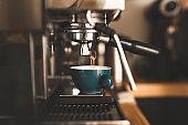 Fresh espresso pouring down into a glass
