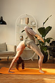 sporty woman doing difficult gymnastic bridge in home interior