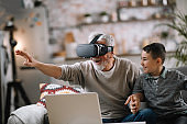 Grandson and his grandpa playing with VR at home on sofa.