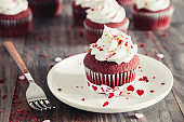 Valentines red velvet cupcakes on a rustic wooden table