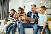 Husband and wife playing video games with kids in living room.