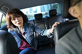 Happy Woman chatting with driver in car