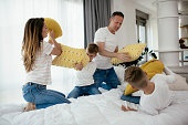 Young parents with sons fighting pillows on the bed