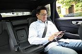 man using a smart phone in a car