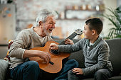 Grandfather and grandson playing guitar.