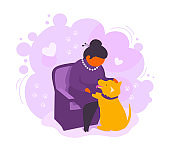 A senior adult woman stroking her dog. Elegant retired lady loves her pet. An elderly puppy owner sitting in an armchair.
