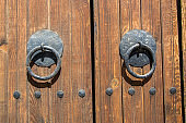 Old wooden massive closed gate. Double door with iron handles and hinges.
