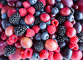 Background of fresh vegetables and fruits. Ripe blackberries, blueberries, plums, pink grapes, raspberries. Mix berries and fruits. Top view. Background berries and fruits. Various fresh summer fruits. Black-blue and red food.