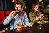 Unhappy young couple sitting in restaurant