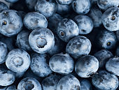 Fresh Blueberry Background. Texture blueberry berries close up. Sprinkle blueberries. Top view. Fresh blueberries scattered. Bunch of blueberries.