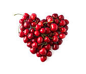 Heart shape red cherries on white background. Background made of cherry. Sweet cherry isolated on white background cutout. Various summer berries. Ripe cherries hill isolated on white. Top view.