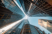 Looking directly up at the skyline of the financial district in central City of London, UK - creative stock image