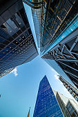 Looking directly up at the skyline of the financial district in central City of London on a bright sunny bright day - creative stock image