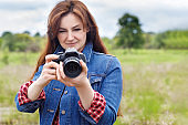 Photographer woman takes pictures with a camera .