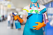 A cleaning lady in a mask holds a spray and a bucket of cleaning products in her hand .