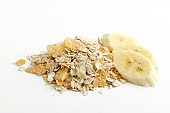 Closeup of heap of oarmeal, corn flakes and slices of delicious banana on the white background.Portion of tasty morning breakfast