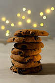 Vertical image.Stack of chocolate cookies on the table against garland bokeh