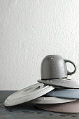 Vertical image.Concept of washing dishes.Stack of wet and clean plates, cup on the grey kitchen table against white wall